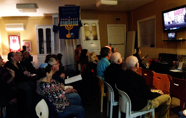 Temple members watch the ordination of Rabbi David via streaming video from Colorado.